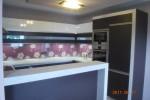kuchnia - fronty dolne folia wenge  fronty górne lakier , uchwyty krawedziowe  a na scienie przeźroczysta szyba zasłaniająca tapetę