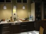 Kuchnia w pastelowych i ciemno-brązowych kolorach oraz klimatycznym oświetleniem